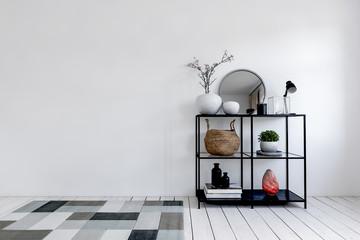Black metal display shelf next to rug on floor