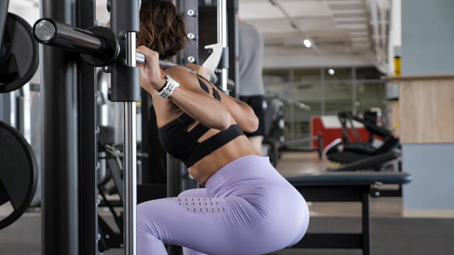 Unrecognizable sportive woman is making squats at Smith rack machine in modern fitness center, side view. Squats with barbell, workout and sport concept.