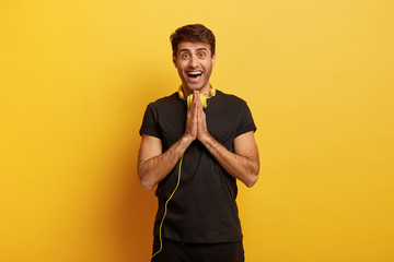 Hopeful cheerful guy presses palms together, hopes for best, asks for help, uses stereo headphones to listen radio online, has glad face expression, wears black clothes, isolated on yellow wall