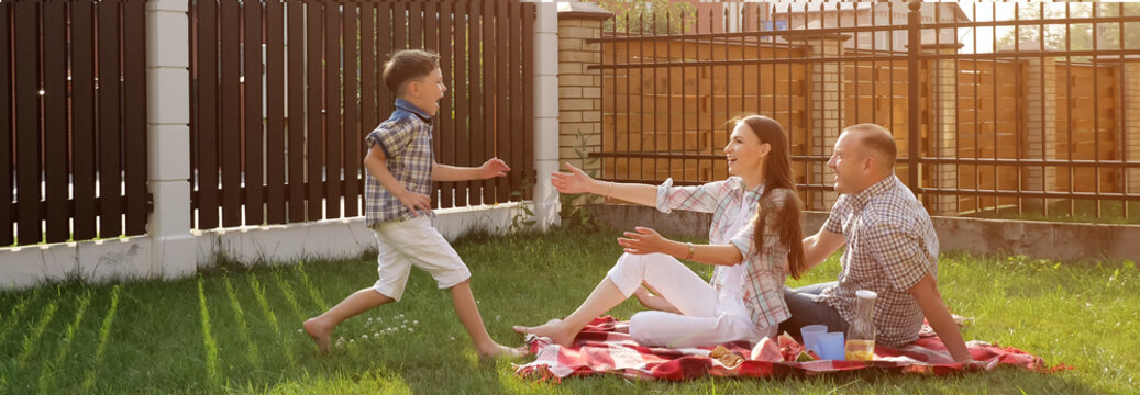 pretty young woman handsome man sit on green yard lawn and happy little son jumps in mother arms close view sunlight