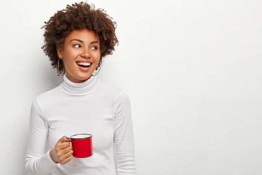 Joyful pleased dark skinned female drinks tea from red cup, looks on right side, glad to have spare time, enjoys coffee break, dressed in casual outfit, isolated on white studio wall, copy space