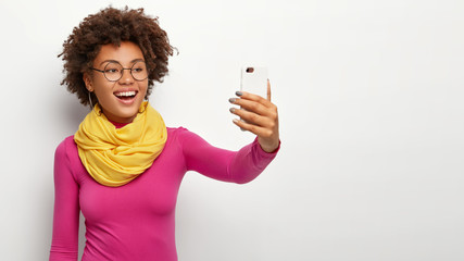 Lovely glad woman smiles broadly, takes selfie portrait on white cell phone, enjoys free time, makes pics for social networks, wears glasses, stylish yellow scarf and rosy jumper, smiles at camera