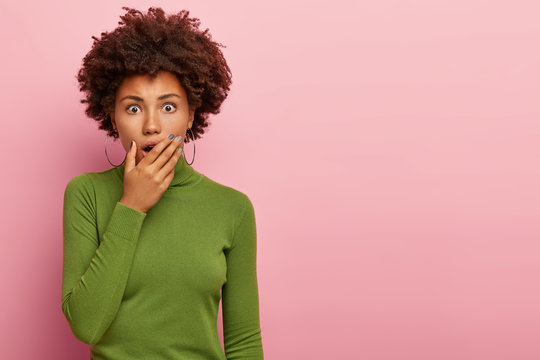 Oh no! Cute young African American girl gasps from fear, looks in terror, covers mouth with palm, learns terrible news, dressed in casual green sweater, models over pink wall with copy space area