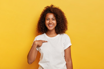 Smiling cheerful dark skinned girl points at herself, shows mockup space on white t shirt, happy being picked, models against yellow background. Carefree delighted young Afro woman asks who me Wall mural
