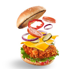 Burger with flying ingredients. Delicious monster Hamburger cheeseburger explosion concept flying ingredients.  Isolated on white