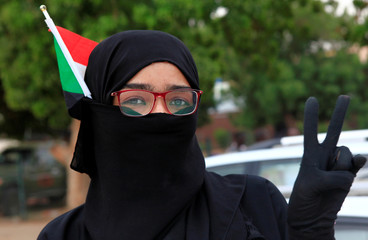A Sudanese woman waves their national flag and flashes a victory sign during celebrations of the signing of the Sudan's power sharing deal in Khartoum