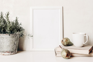 White vertical blank wooden frame mockup. Composition of rosemary herb in old metal flower pot, books, cup of coffee and pears on white table. Home decor. Rustic summer poster product design.
