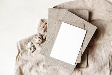 Feminine stationery, desktop mock-up scene. Blank greeting card, craft envelope, sea shells and old books on beige linen tablecloth background. Flat lay, top view. Summer rustic composition.