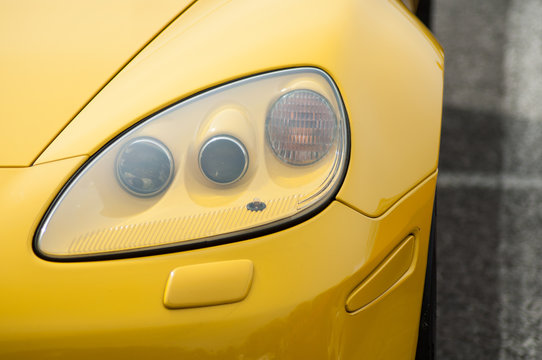 Closeup of  vintage american yellow Corvette front light parked at fun car show event