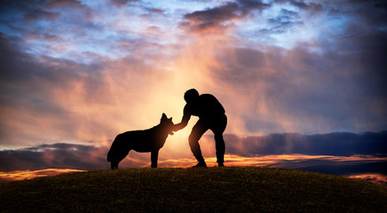 Silhouette of a man caressing his dog on a hill at sunset.