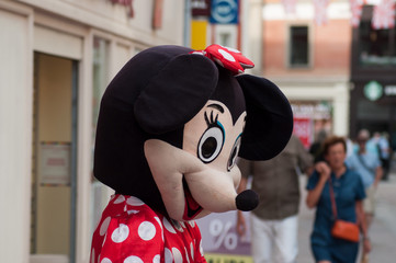people with Minnie mouse costume in the street