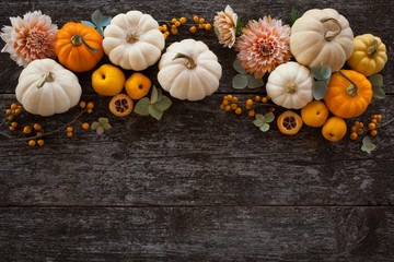 Wooden background with pumpkins and flowers