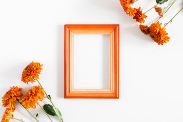 Autumn creative composition. Photo frame, orange flowers on white background. Fall concept. Autumn background. Flat lay, top view, copy space