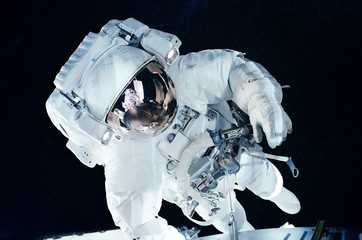 Astronaut in open dark space. Elements of this image were furnished by NASA