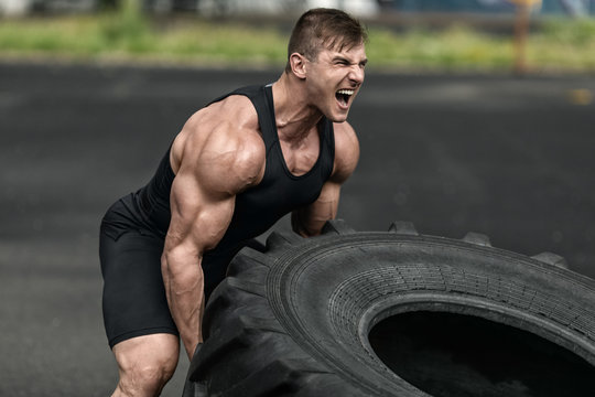 Muscular man working out flipping tire, outdoor. Strong male crossfit training