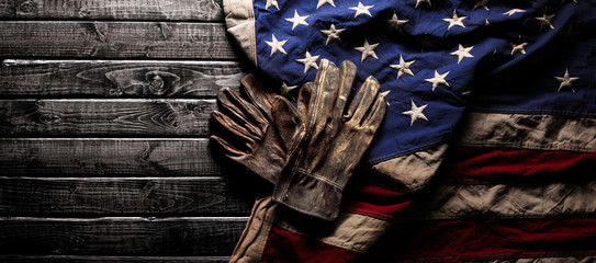 Old and worn work gloves on large American flag - Labor day background