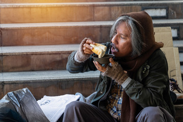 Homeless man is sitting down on staircase in town.He is eat bread and milk.He is very hungry and unhappy.poverty,despair, Photo Sympathetic and hope concept.