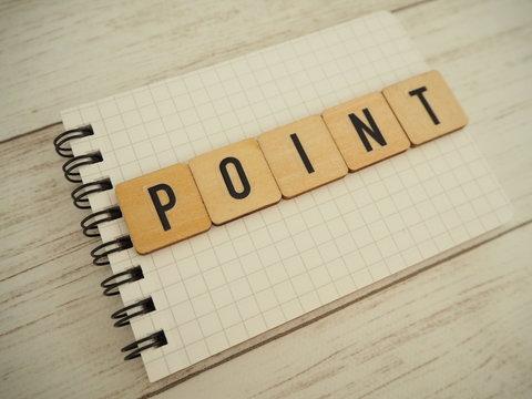 ノートの上に木製ブロックでポイントの単語