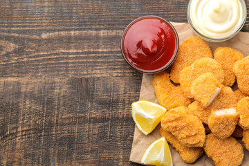 Chicken nuggets with red and white sauce and lemon on a brown wooden table. fast food. top view.