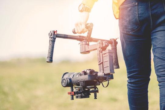 Videographer holds electronic stabilizer steadicam gimbal for DSLR camera