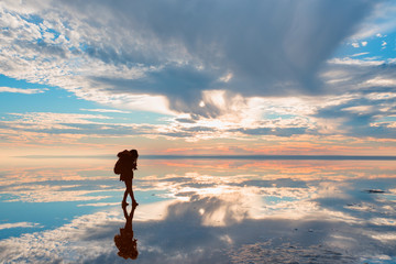 Silhouette of photographer takes a photo at amazing sunset with reflected waters