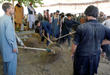 Men shovel dirt over the coffins of the victims of a blast in a wedding at a burial ceremony in Kabul
