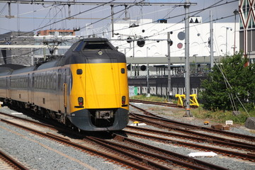 Yellow blue intercity train at the station of the city Gouda heading to Utrecht