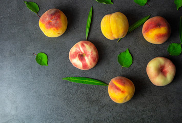 Nice yummy fresh peaches with green tree leaves on dark texture surface. Top view. Summer fruits.
