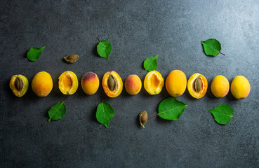 Nice yummy fresh sliced apricots with green tree leaves stay in lines on dark texture surface. Summer fruits. Top view.