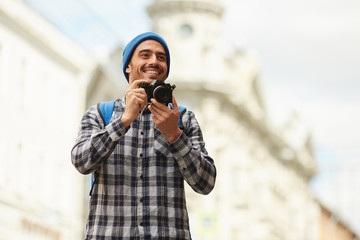 Waist up portrait of smiling young tourist holding map looking at directions while enjoying solo trip in Europe, copy space