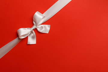 Wall Mural - Shiny white ribbon bow on red