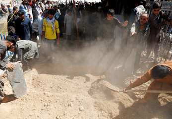 Men shovel dirt as they take part in a burial ceremony of the victims of a suicide bomb blast at a wedding in Kabul