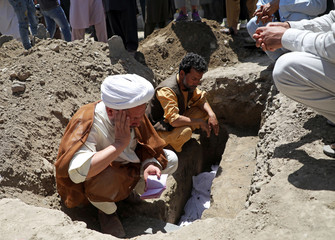 An Afghan cleric reads the holy Koran over the grave of a civilian during a burial ceremony after a suicide bomb blast at a wedding in Kabul