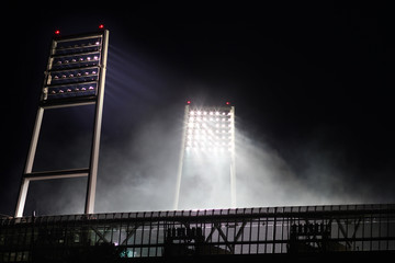 floodlight of the weser stadion at gametime at night with smoke