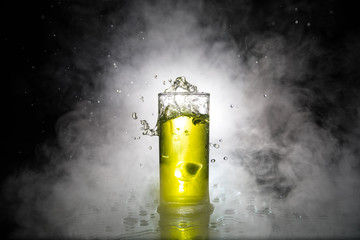 Cocktail glass splashing on dark toned smoky background or colorful cocktail in glass. Party club entertainment. Mixed light.