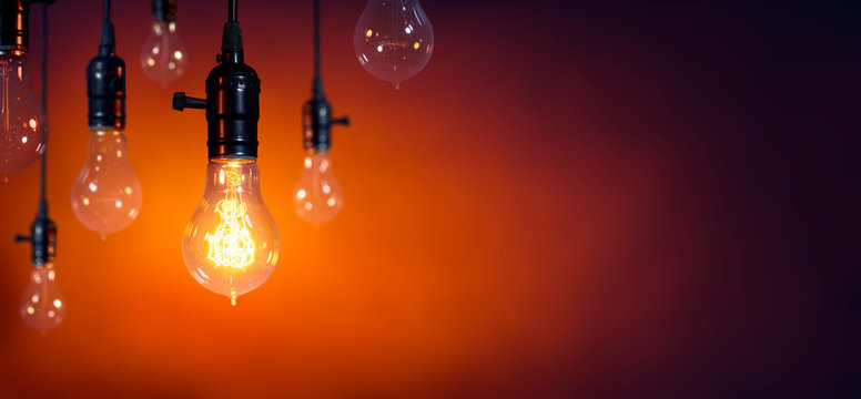 Leadership And Innovation Concept - Standing Out From The Crowd - Glowing Bulb On Among Bulbs Off