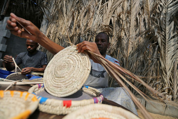 Members of a Palestinian family make traditional decorative objects with palm tree leaves to be sold in the local market, in the central Gaza Strip