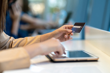 Closeup Asian woman using credit card with tablet for online shopping in department store over the clothes shop store background, technology money wallet and online payment concept, credit card mockup Fototapete