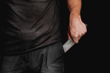 Man's hand holds a knife on black background. topics of violence and murder. thief, killer, rapist, maniac Fototapete