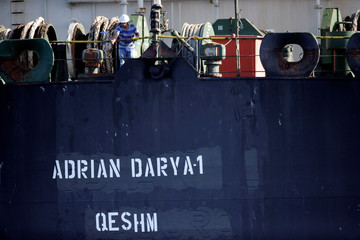 A crew member takes pictures with a mobile phone of Iranian oil tanker Adrian Darya 1, previously named Grace 1, as it sits anchored after the Supreme Court of the British territory lifted its detention order, in the Strait of Gibraltar
