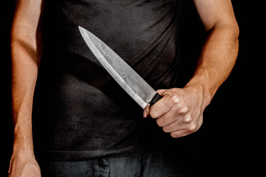 Man's hand holds a knife on black background. topics of violence and murder. thief, killer, rapist, maniac
