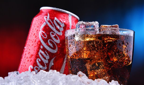 A glass and a can of Coca-Cola