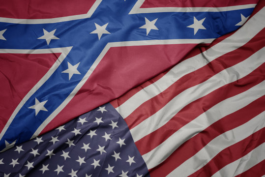 waving colorful flag of united states of america and confederate flag
