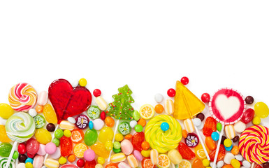 Fototapete - Colorful lollipops and different colorful candy isolated on white