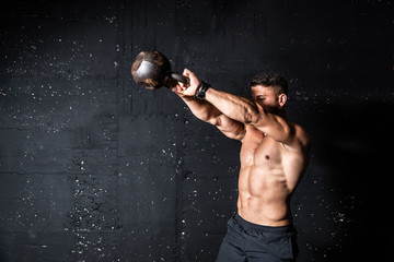 Young strong sweaty focused fit muscular man with big muscles holding heavy kettle bell for swing training hard core workout in the gym