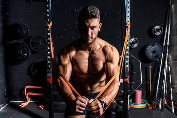 Young strong focused fit muscular man chest stretching workout in improvised gym with rubber for strength and good looking of muscles dark image