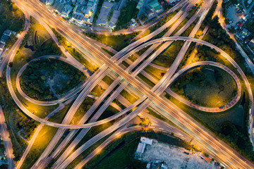 Fotobehang Nacht snelweg Aerial view of illuminated road interchange or highway intersection with busy urban traffic speeding on the road at night. Junction network of transportation taken by drone.