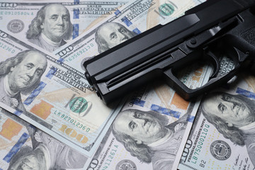 Pistol gun on 100 us dollar banknote,illegal money by gangster dirty job criminal and terrorism concept