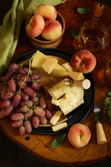 cheese, grapes and wine on a wooden table, rustic style