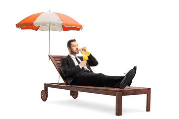 Young businessman in a suit lying on a sunbed under umbrella and sipping a cocktail